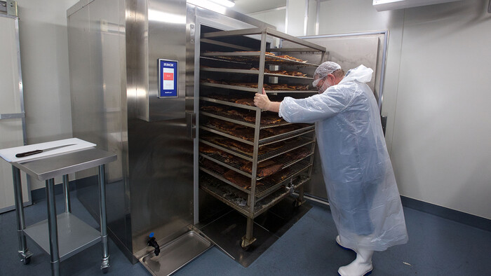 Removing the smoked meat from the meat smoker at Texas BBQ Foods